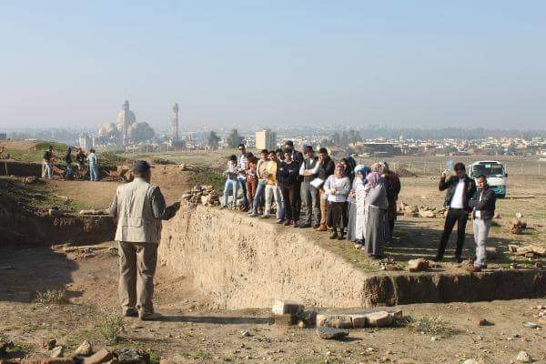 Students and faculty members from the University of Mosul's College of Archaeology inspect a dig on the outskirts of Mosul (Photo courtesy of U. of Mosul Public Relations Department).