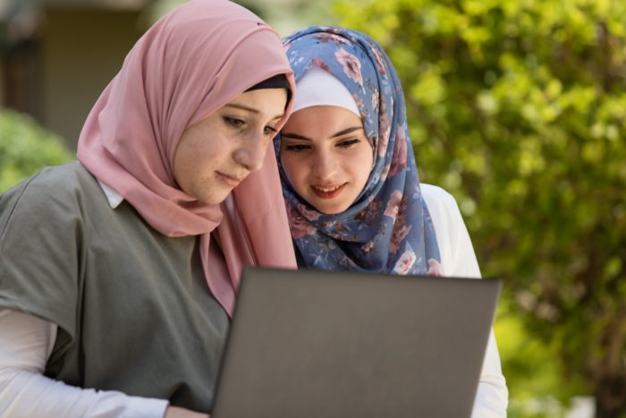 Two HOPES scholarship recipients share a computer screen during a 2019 gathering (Photo: Madad-HOPES).