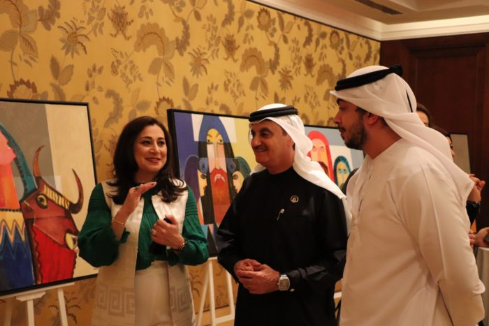 The artist explains her ideas to visitors to her first solo exhibition in Dubai in 2019. The painting shows a bull-headed Sumerian lyre (Photo courtesy of Zeana Atarbashi).