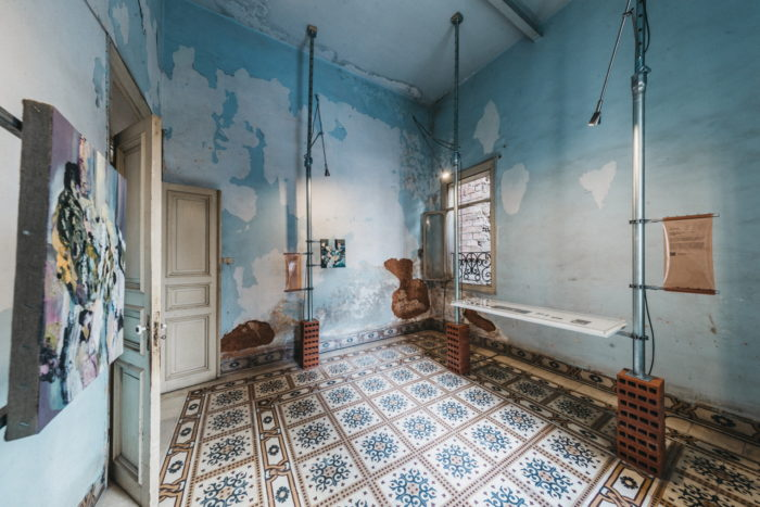 Hatem Imam's series Cataract is displayed in a room with faded blue walls.
