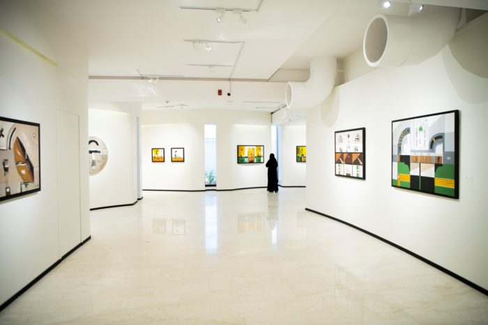 A visitor views paintings by Abdulrahman Al Soliman in an exhibition at the Misk Art Institute that also features works by Adam Henein.