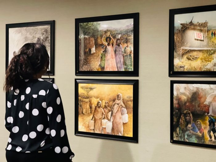 At an exhibition of Hemoudi's paintings in Northern Virginia, a visitor looks at works depicting rural life in Sudan.
