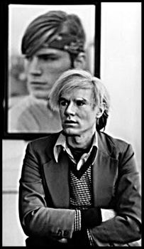 20160920004906-andy_warhol_at_desk_with_joe_dallesandro_behind__warhol_s_ny_studio__1976__courtesy_of_michael_childers_