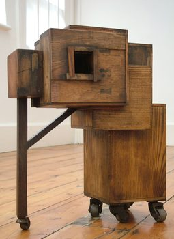 20170116210206-crutch_and_tumour_box_brown_wood_found_materials_box_sculptures_on_wheels_by_artist_wayne_chisnall