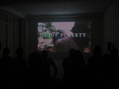 Enjoy_poverty_-_renzo_martens_-_video_work_at_the_biennale_xberg_site