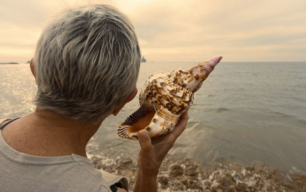 a woman holding a seashell to her right ear