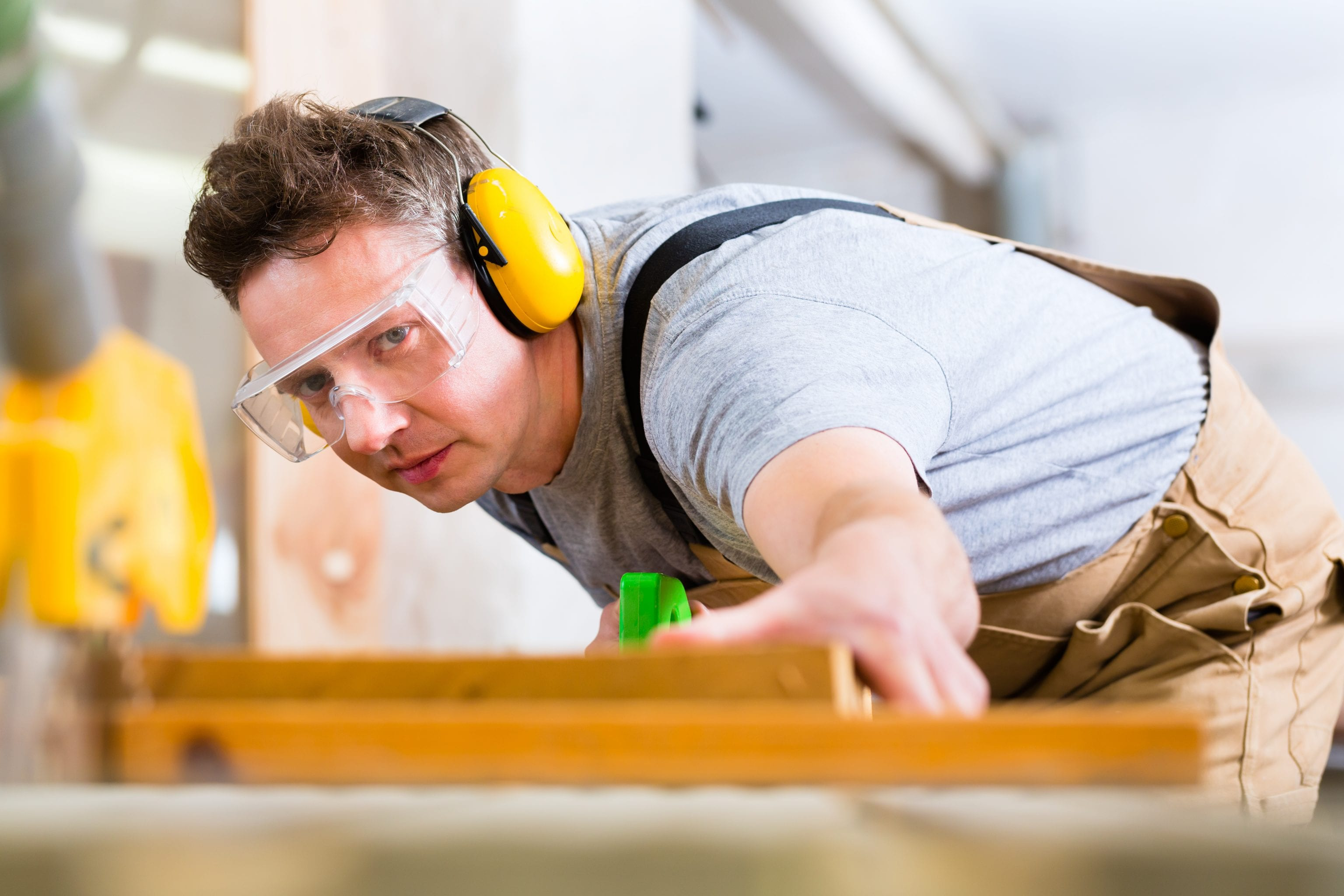 man in carpentry shop sawing wood and wearing ear protection