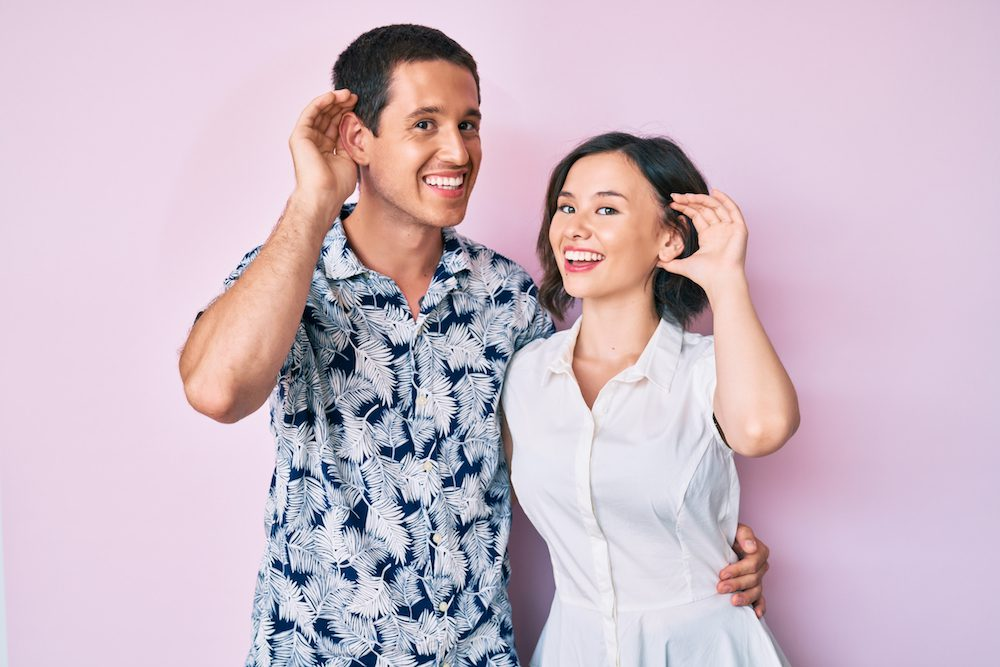 Beautiful couple wearing casual clothes smiling with hand over ear listening an hearing to rumor or gossip. deafness concept.