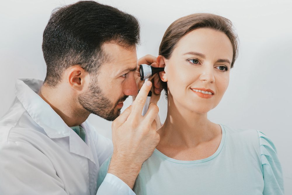 side angle image of hearing specialist testing hearing of patient