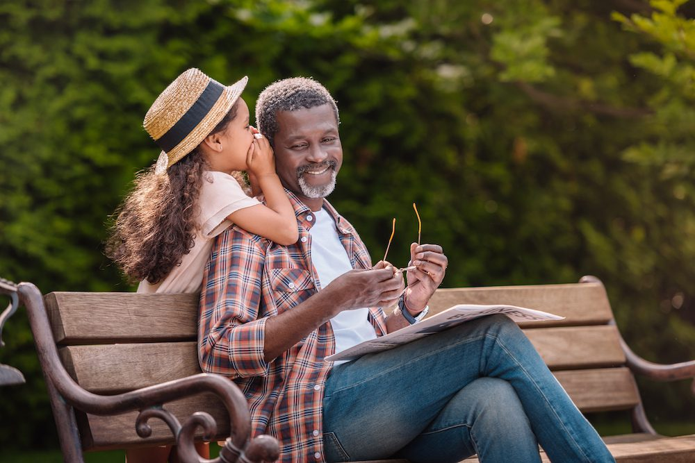 daughter whispering something to father sitting on bench