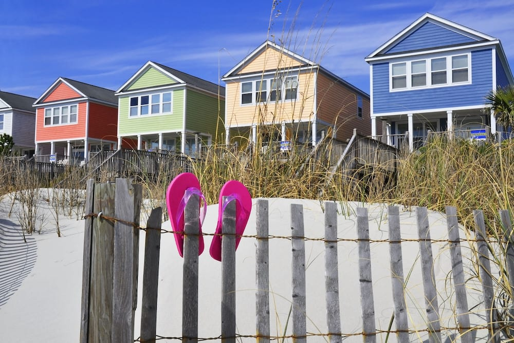 four houses on beachfront with white sand and pink sandals