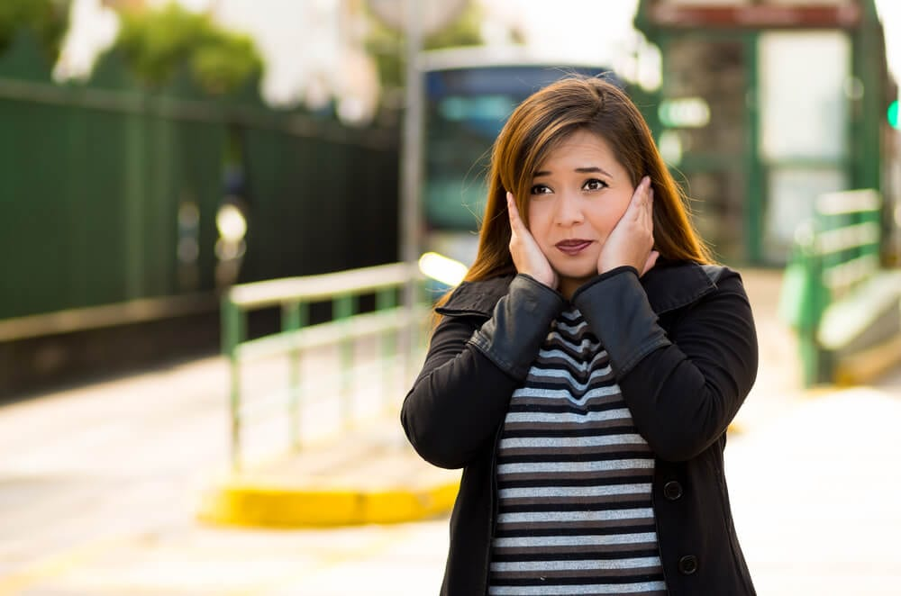 woman covering her ears with both hands on the street