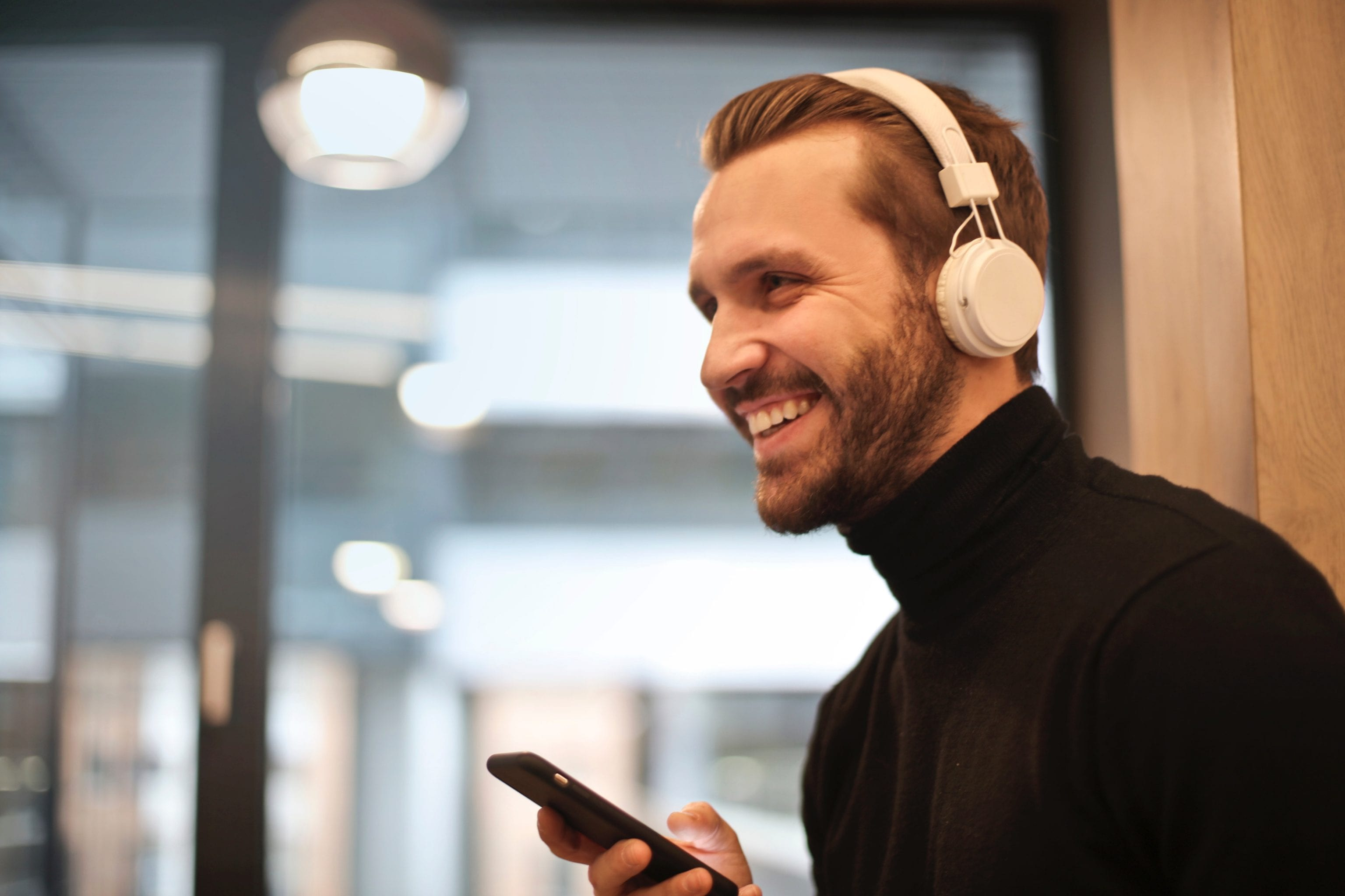 a man with facial hair is holding his phone and listening to music