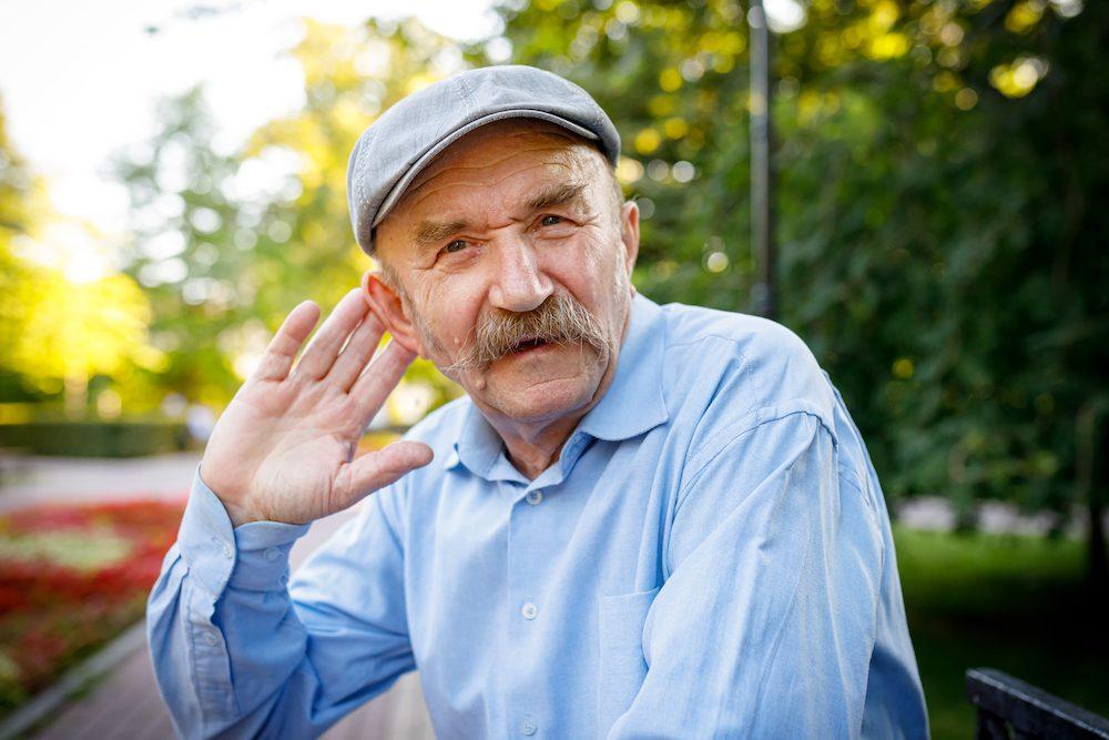 Elderly man tries to hear. An expressive gesture.