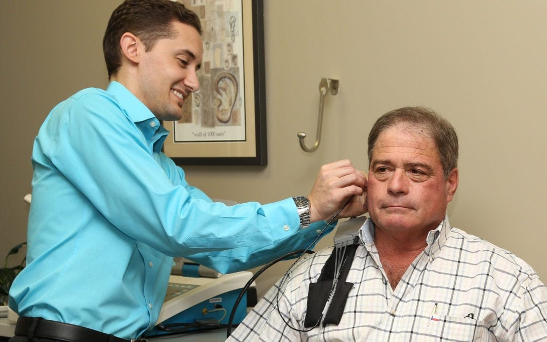 an audiologist giving his patient an ear examination