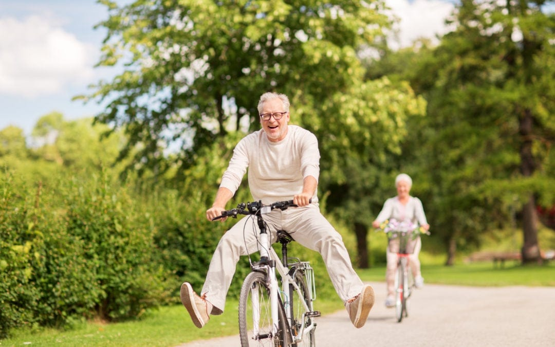 an older man having fun outside on a bicycle