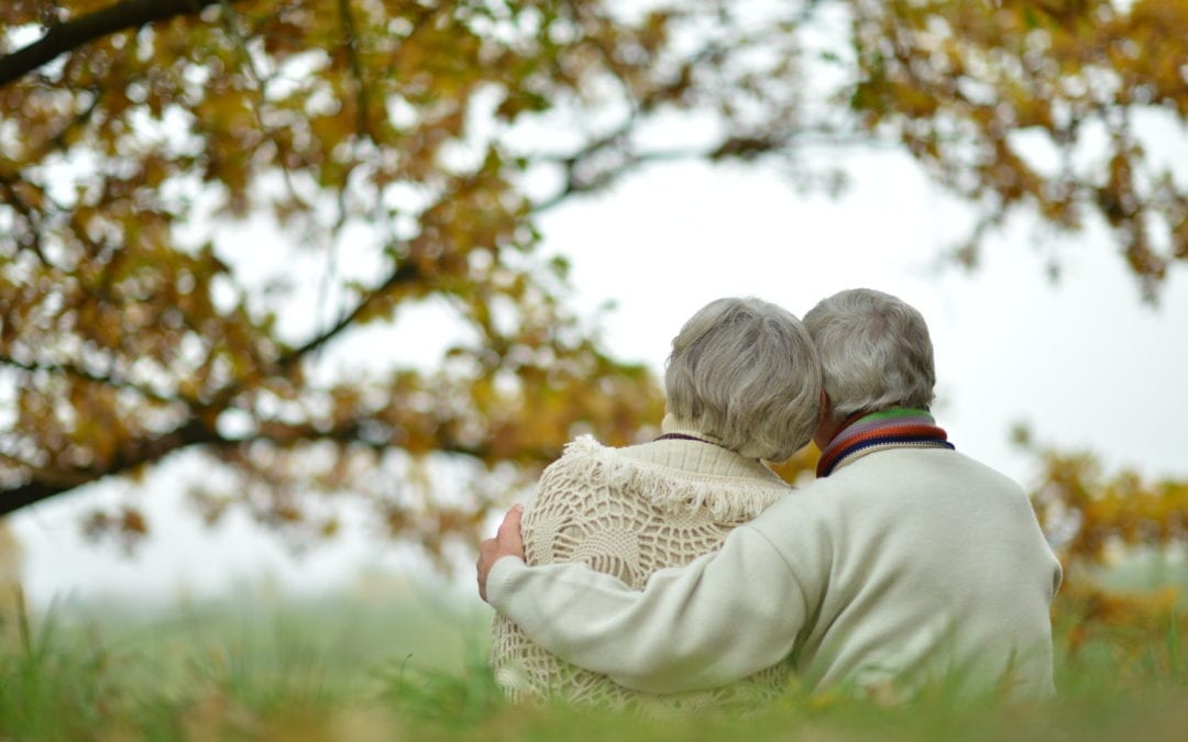 Elderly couple hugging sat otuside 1080x675 1