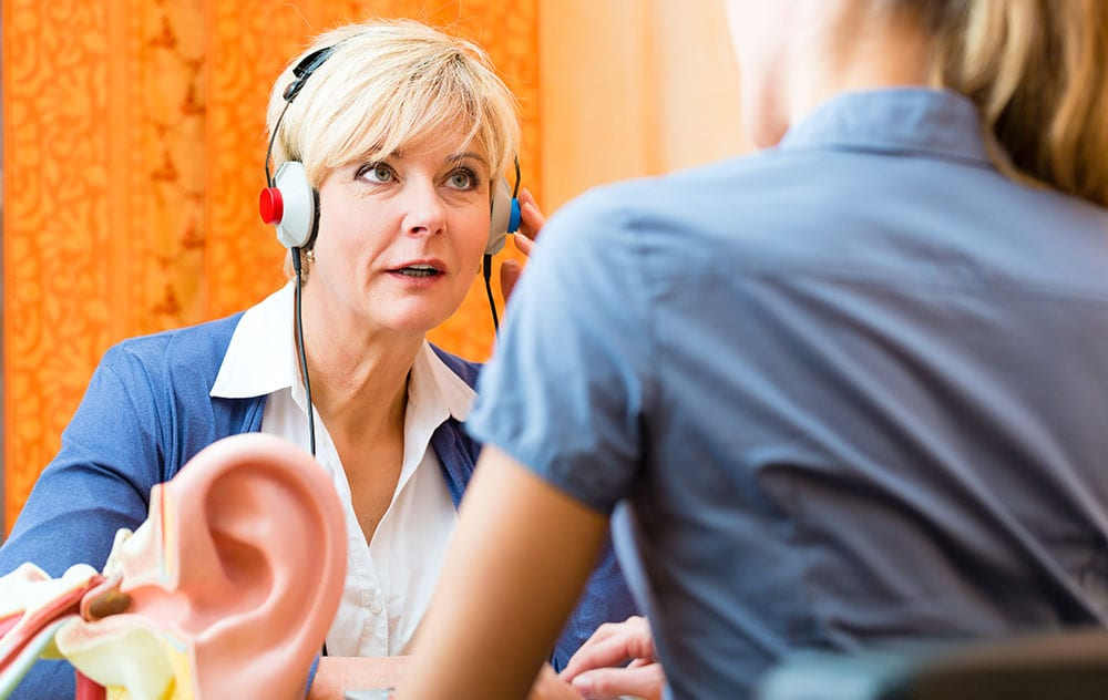 a woman receiving a professional hearing test