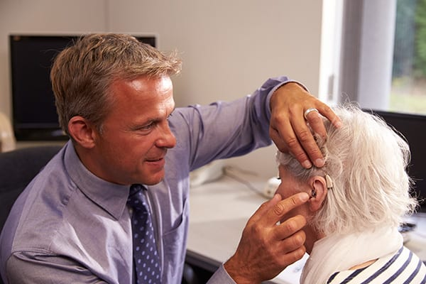 a hearing specialist performing a hearing aid fitting for his elderly patient