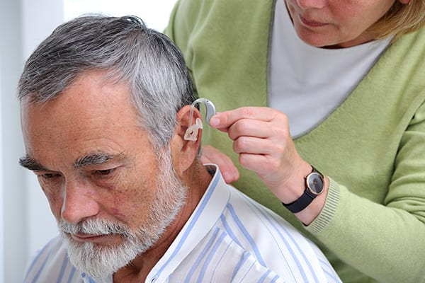 an older man being fitted for new hearing aid models