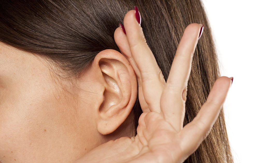 a brown haired woman cupping her hand to her ear