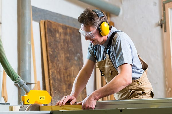 middle aged man cutting wood in garage while wearing ear protection