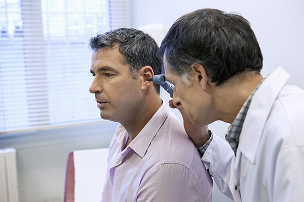 a hearing specialist examining his patient's ear