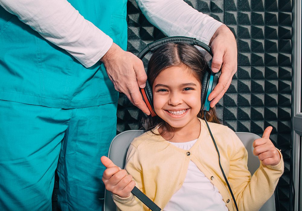enthusiastic girl having her ears tested by hearing specialist