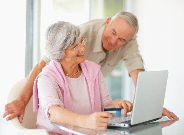 couple researching local audiologist on laptop in bright room