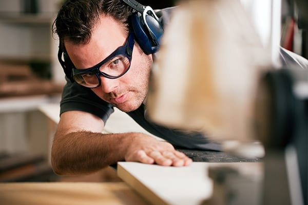 a man cutting wood while wearing over the head hearing protection
