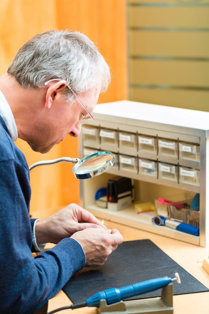 man repairing broken set of hearing aid devices