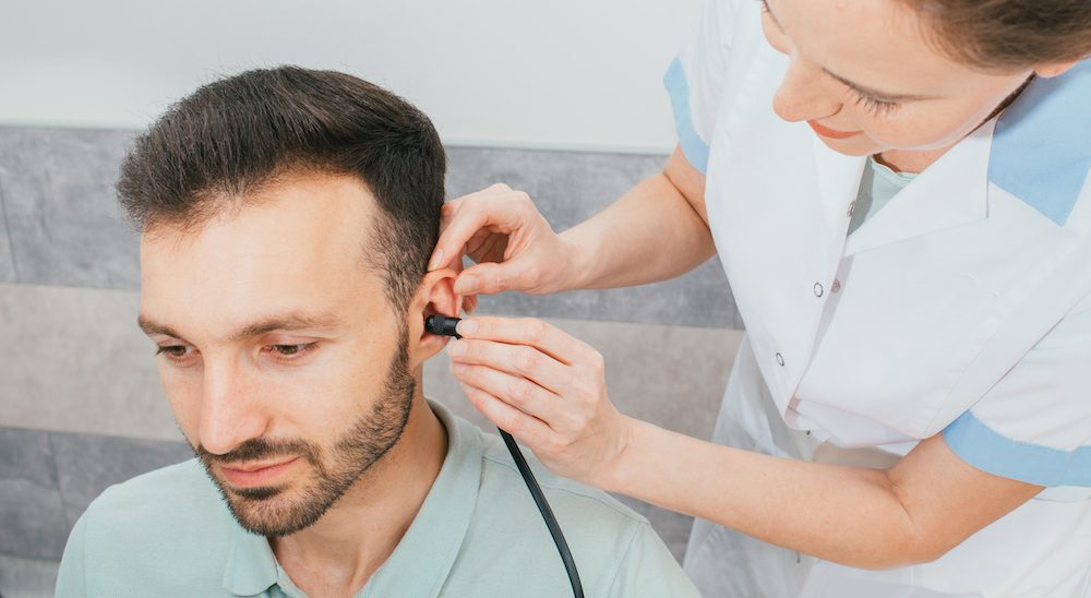 hearing specialist fitting new hearing aids for hearing loss patient