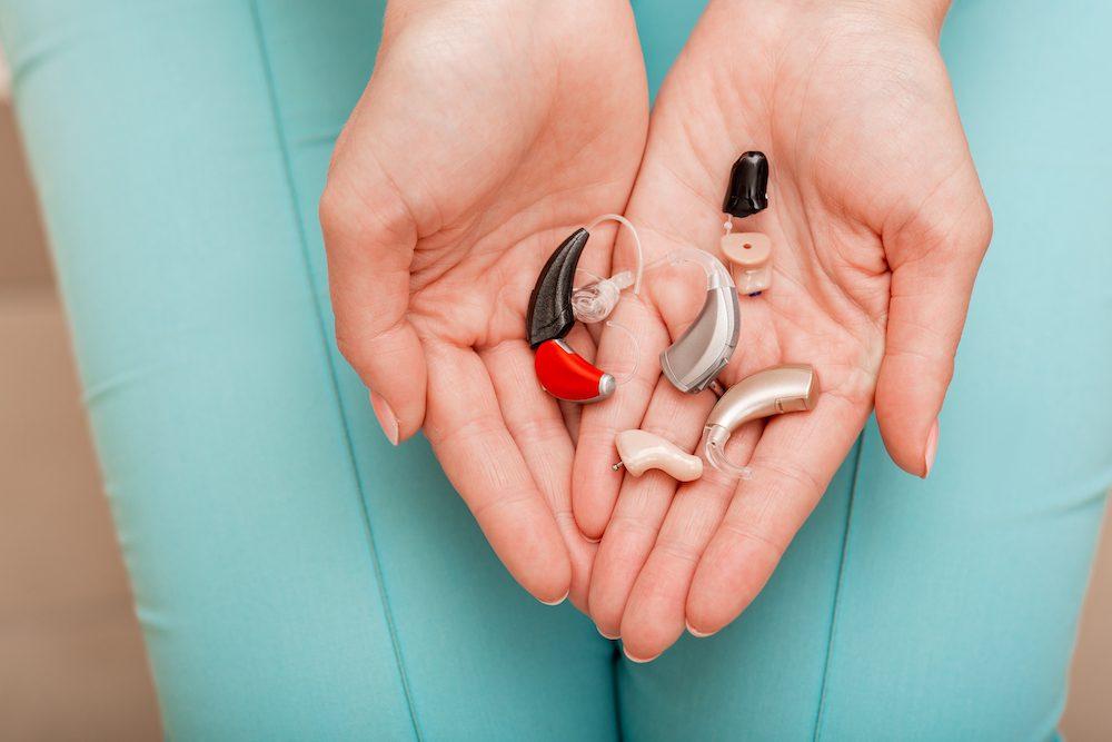 bunch of hearing aids held in hands