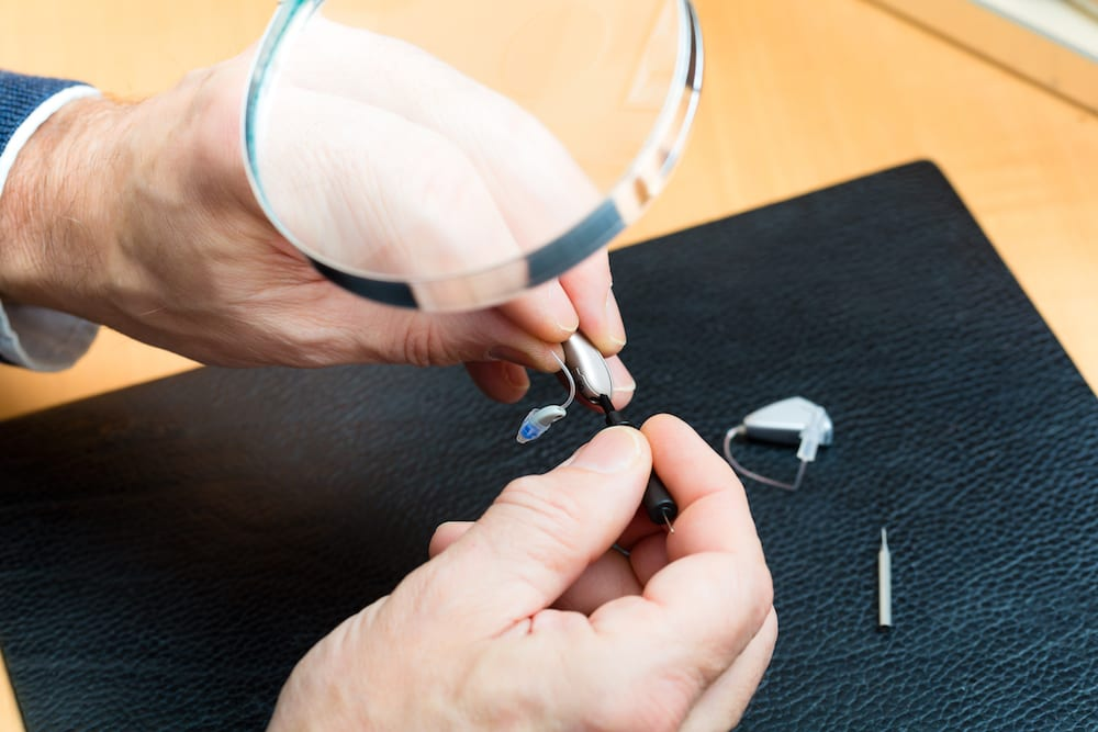 a hearing aid being repaired under a magnifying glass