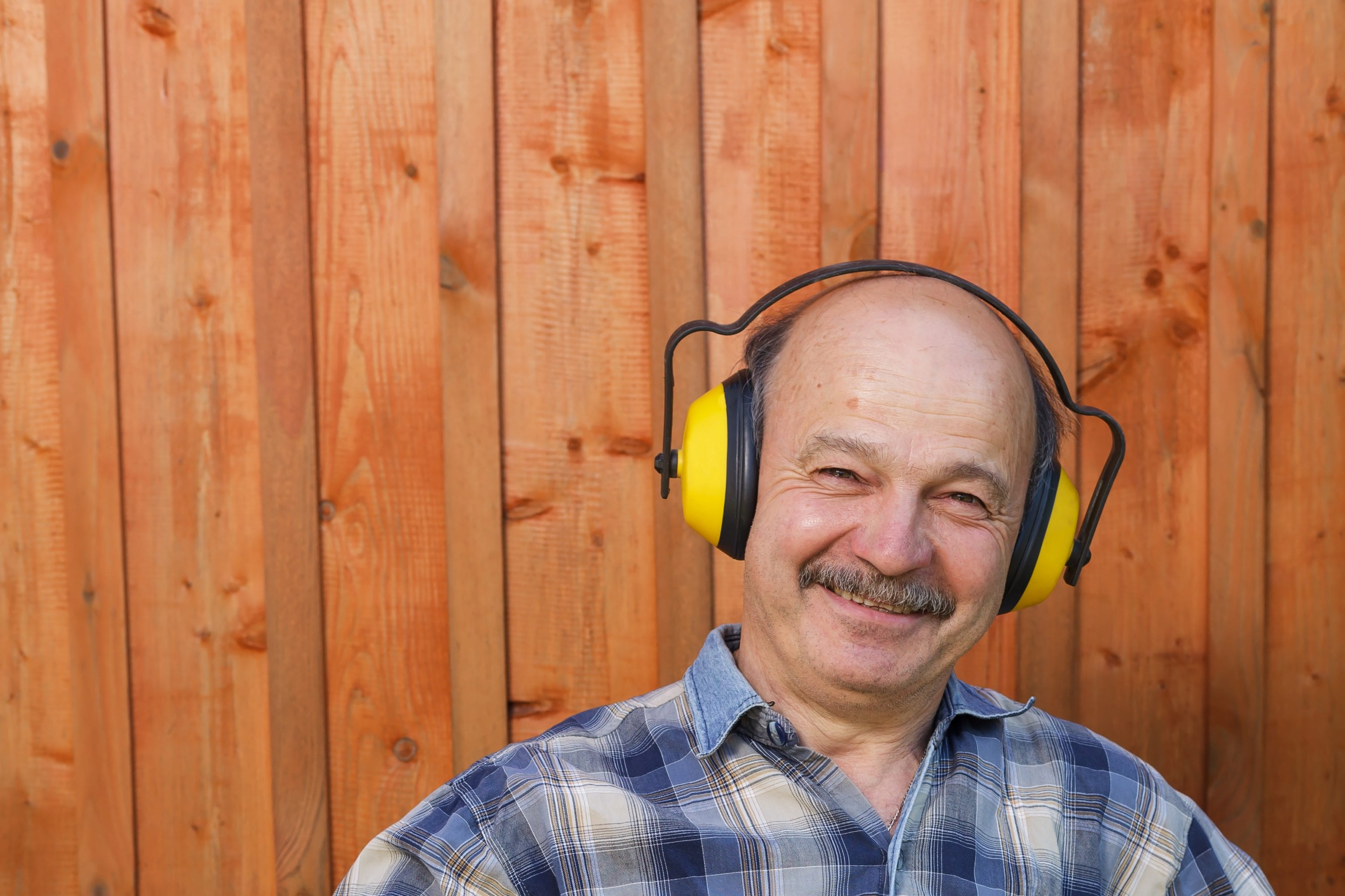 smiling man in plaid shirt wearing yellow over-the-head hearing protection device