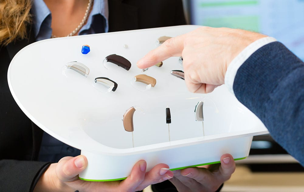 a hearing specialist is selling new hearing aids to a patient
