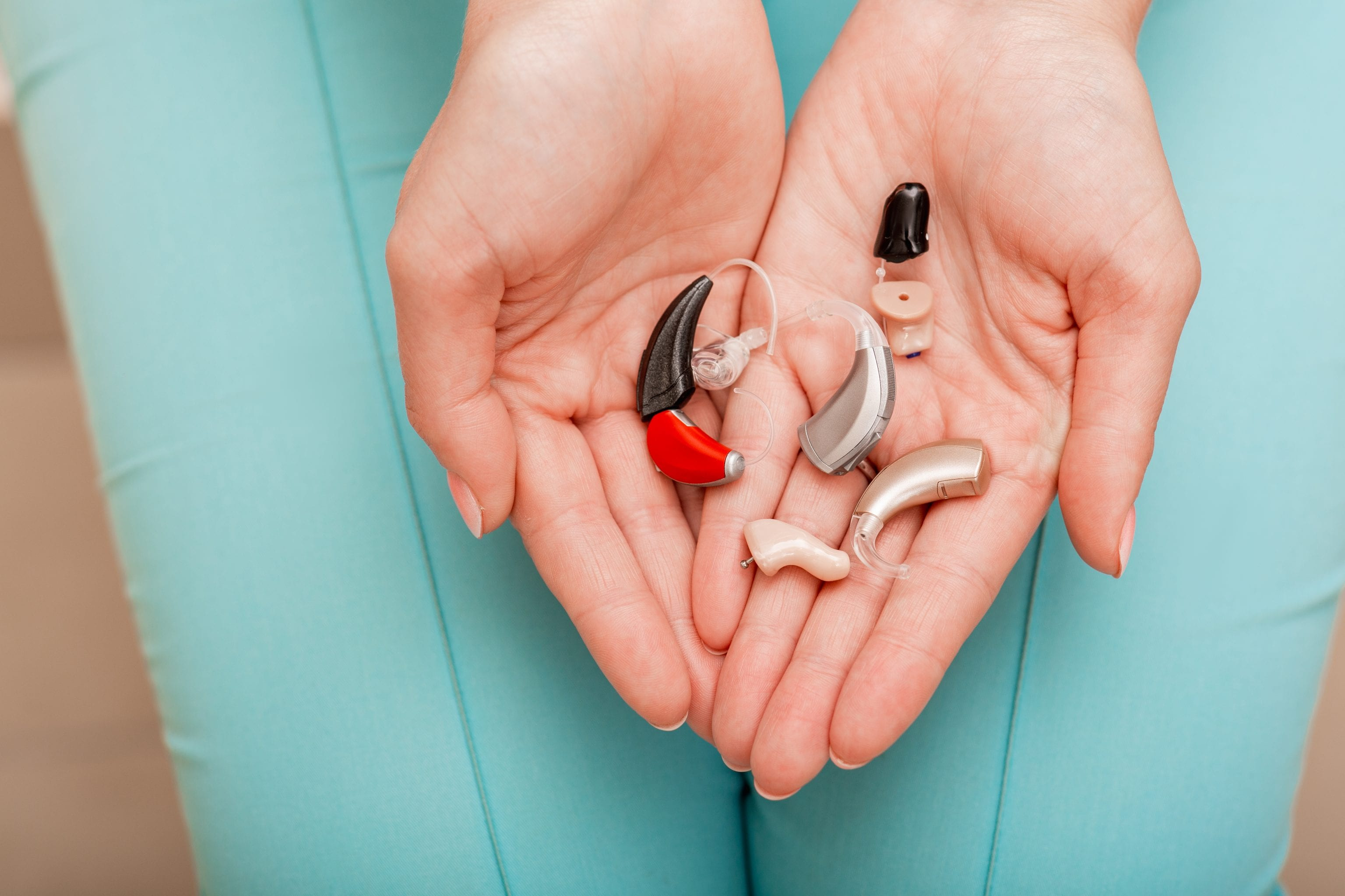 two hands holding pile of hearing aid devices