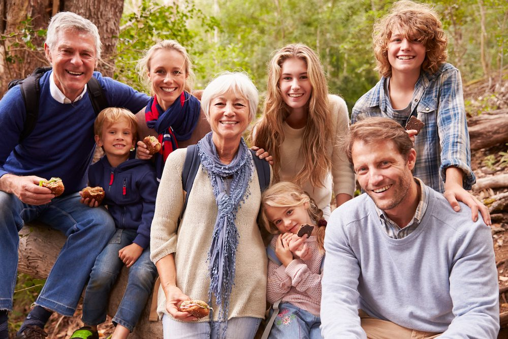 family of all ages gathered in woods for group photo