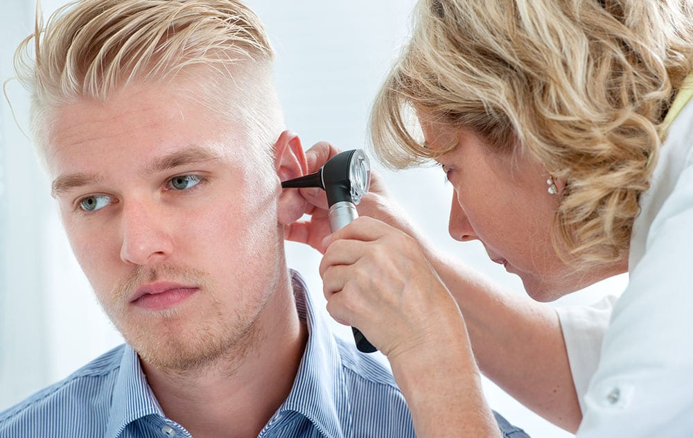 a blond haired man getting his ears examined