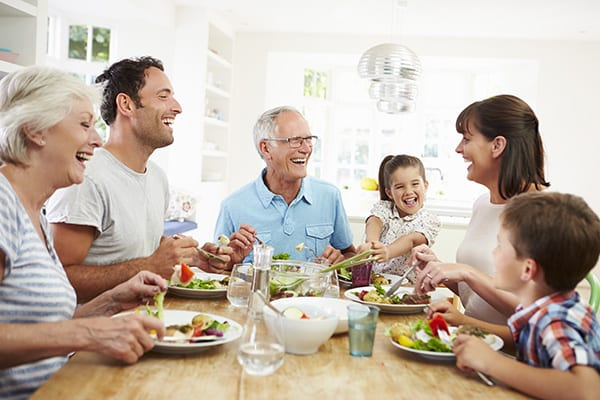 a happy family eating dinner and laughing