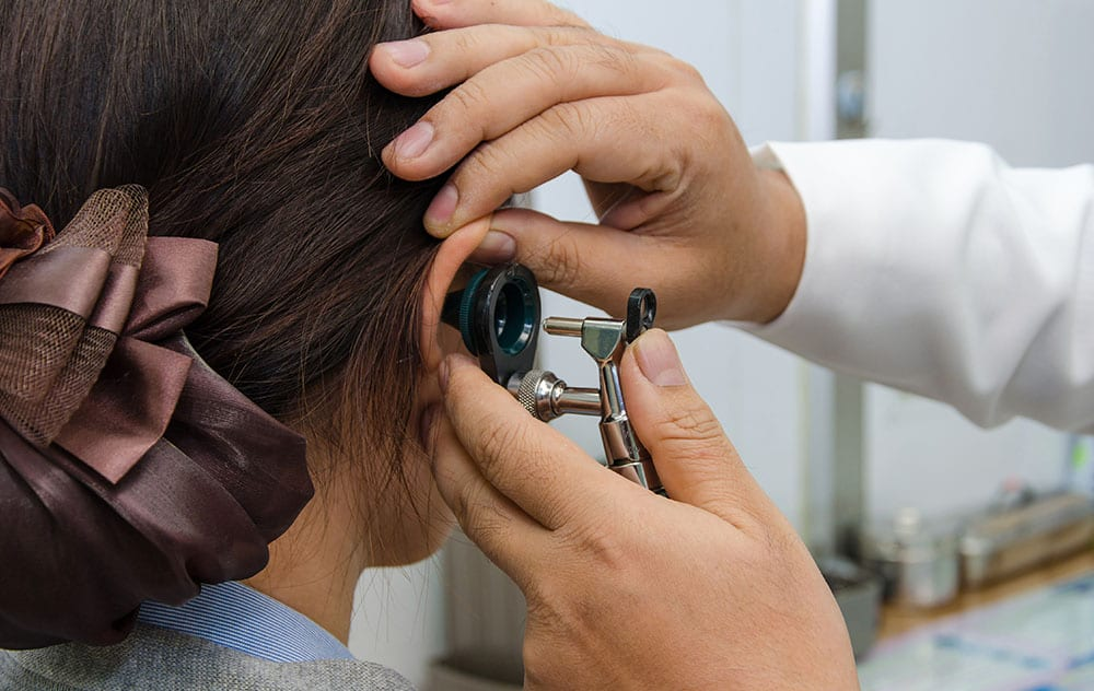 an audiologist administering a basic hearing checkup