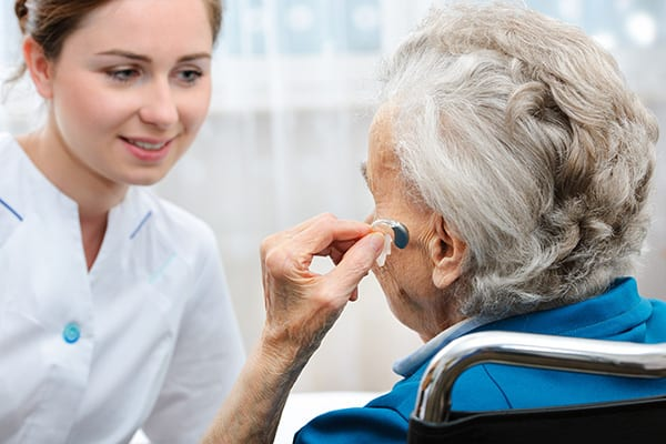 an older woman inserting a hearing aid into her left ear
