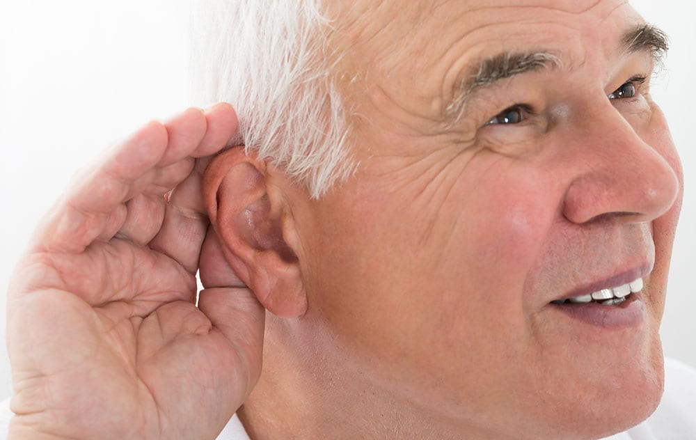 an older gentleman struggling to hear by cupping a hand to his ear