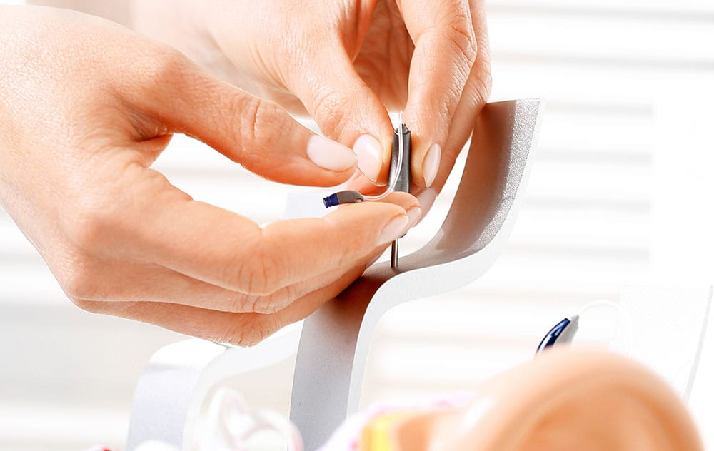 a manicured hand holding a hearing aid on a display stand