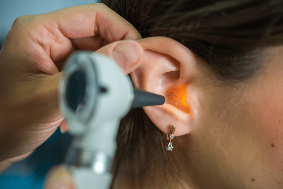 an audiologist using a specialized ear doctors tool to examine a patients ear