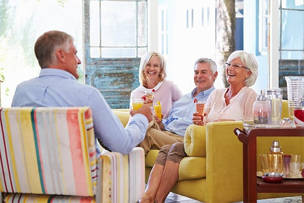 two couples conversing over brunch in a well-lit room