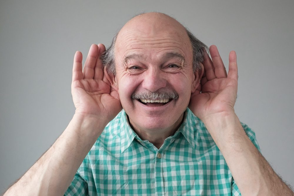 smiling man cupping hand to both ears