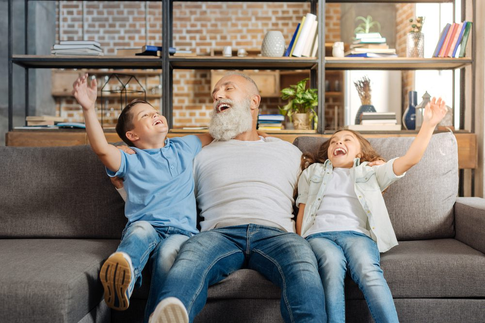father playing with his children on couch