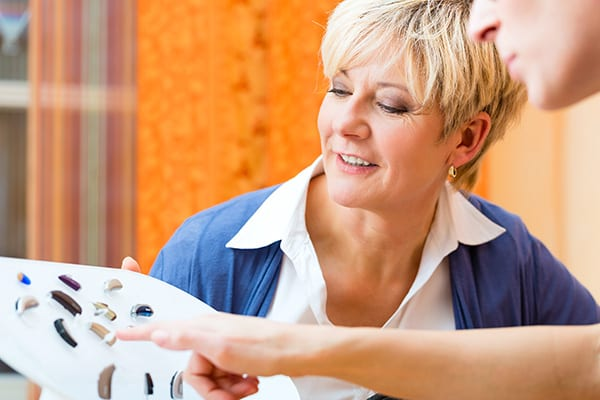 a smiling woman with a positive attitude is selecting hearing aids
