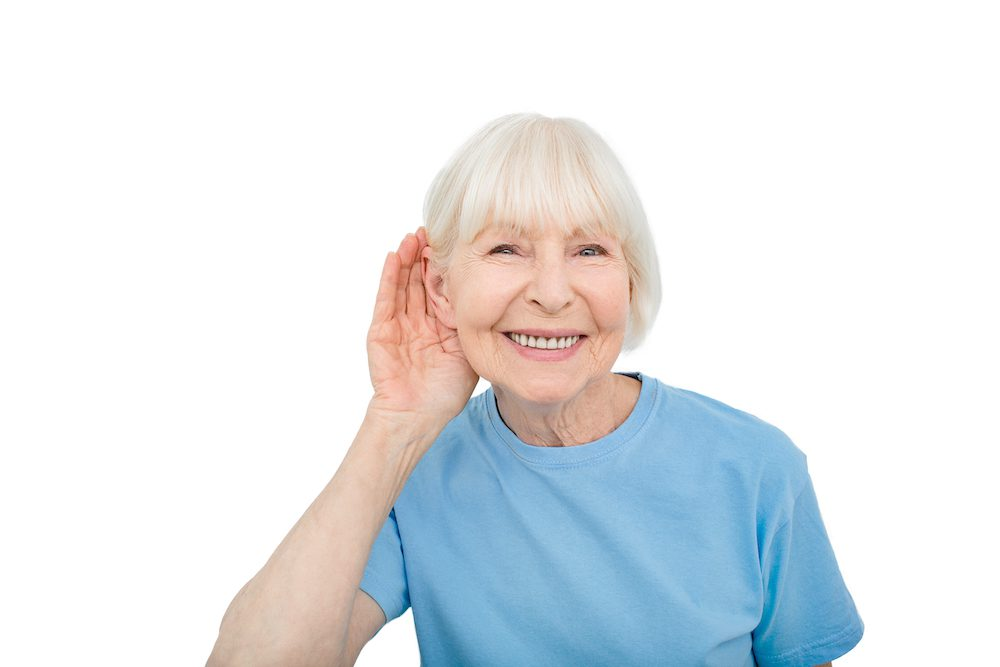 elderly patient in blue t shirt cupping hand to ear to hear better